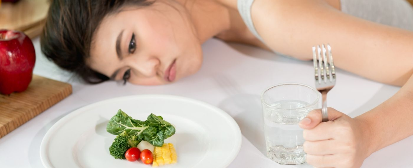 A frustrated woman stares at a spare plate of veggies in hunger