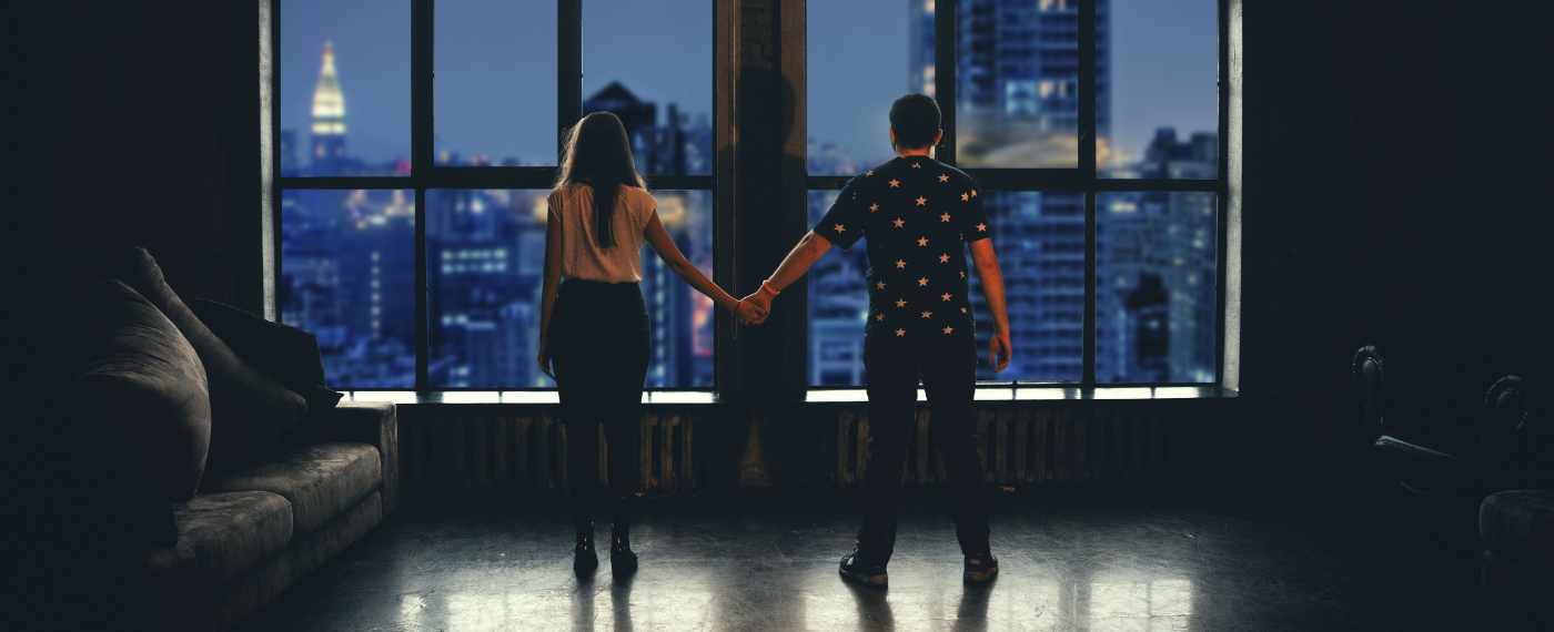 Woman and man holding hands overlooking city scape