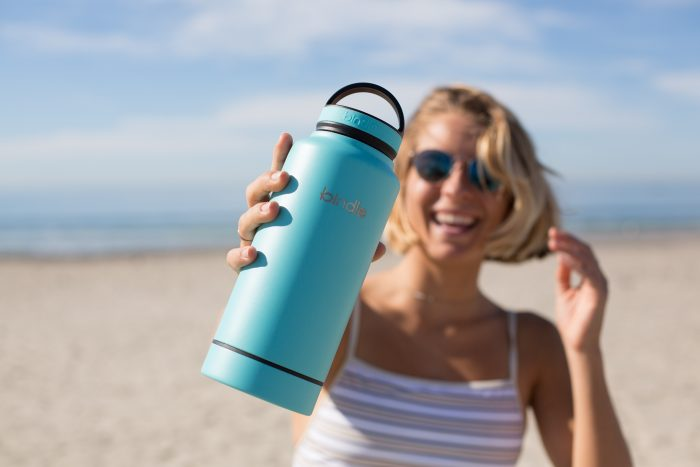 Woman smiles while holding up traveling water container
