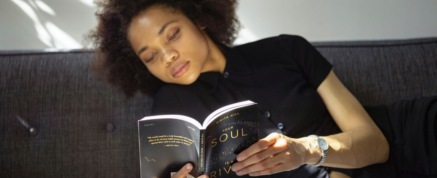 Woman leans over reading a book about being kind to yourself