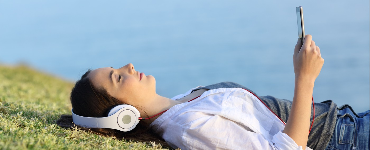 Girl lying on a grassy field with headphones listening to meditation playlist