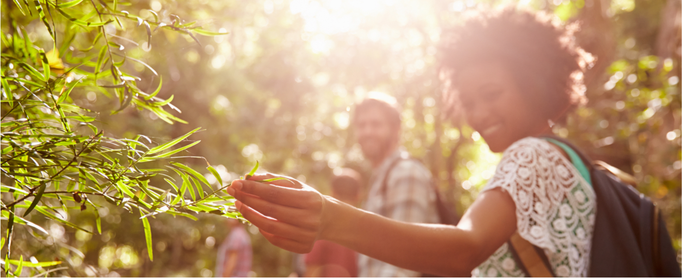 A woman hikes in nature with friends to relieve stress