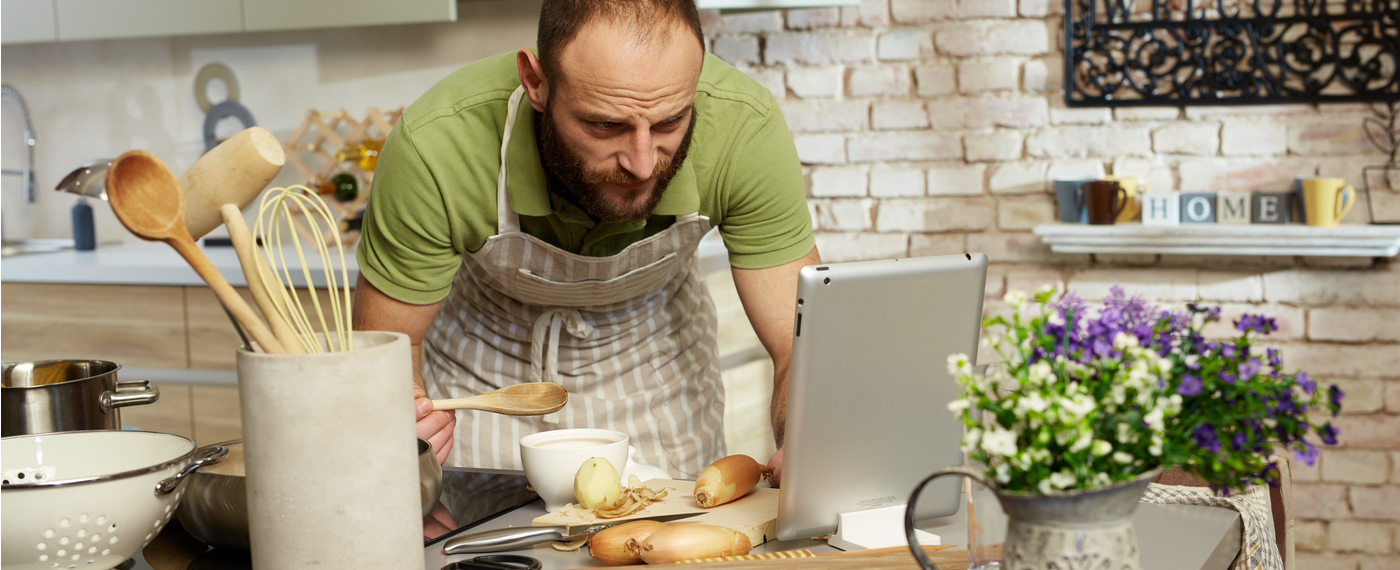 A man prepares food based on a recipe from the Internet