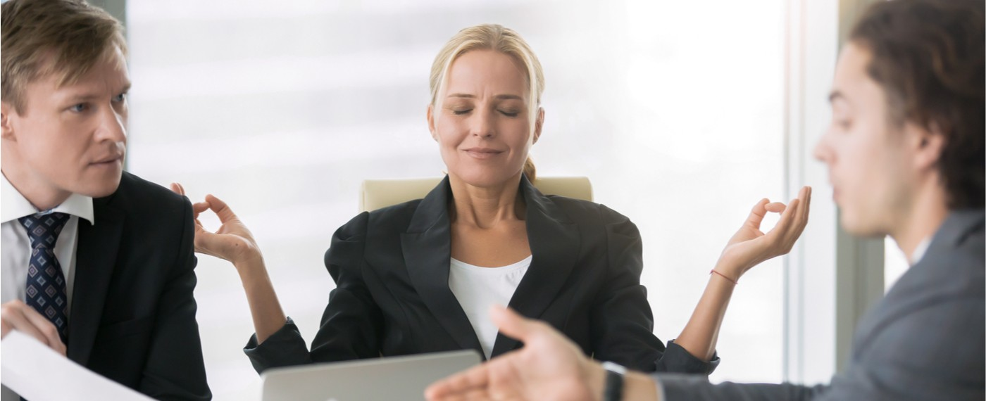 female coworker humorously meditates while male coworkers argue