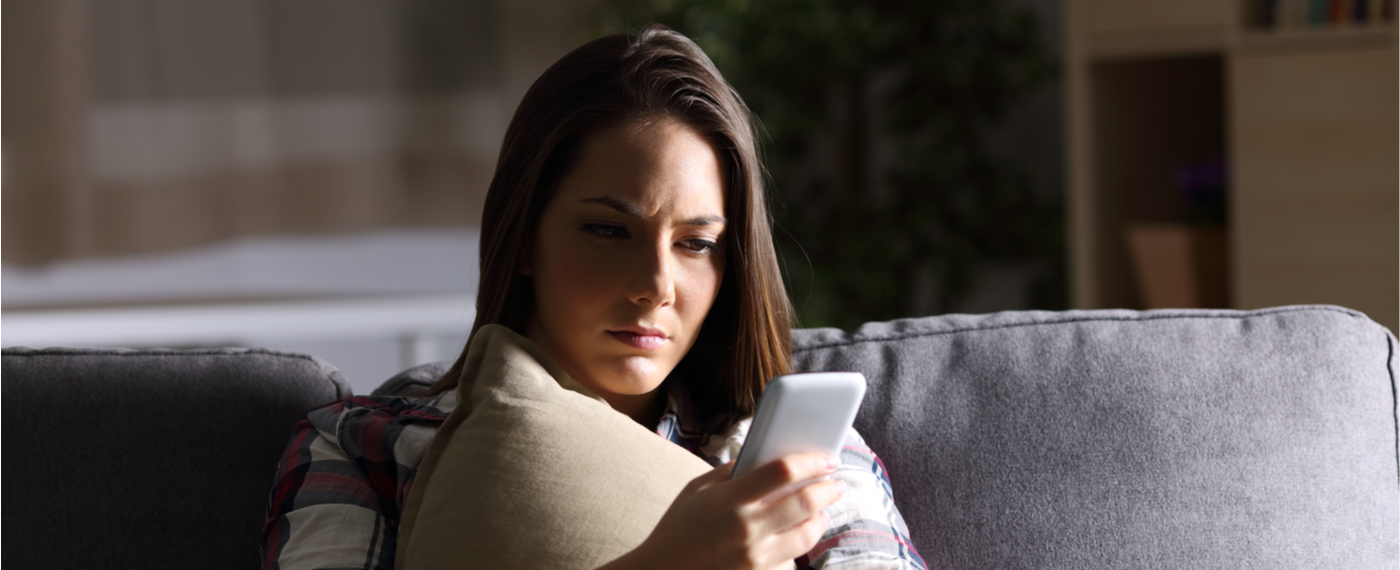 Woman looking upset at phone after being ghosted by friends
