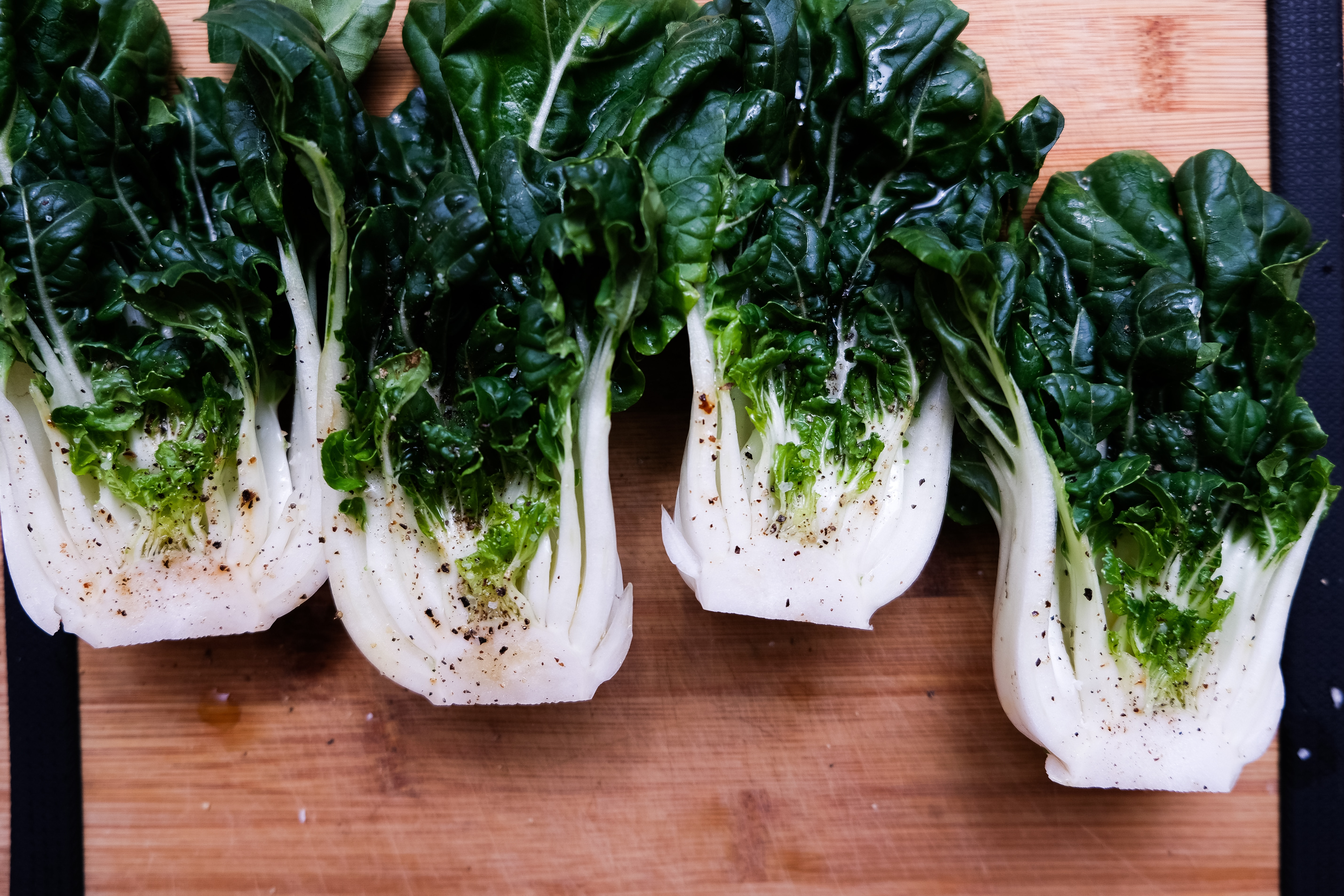 Four pieces of Bok Choy on a wooden cutting board