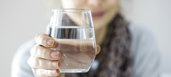 A woman holding a glass of water to promote gut health
