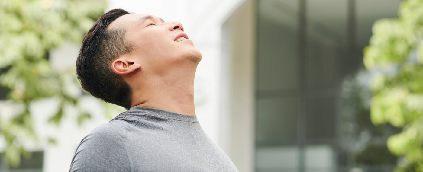 Man outside with head tilted back towards the sky