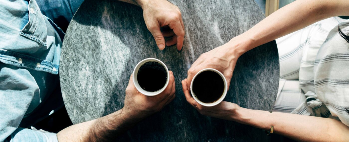 Two men sitting at table with cups of coffee