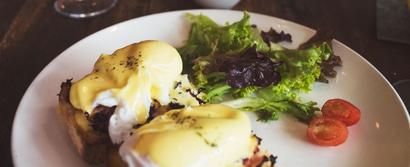 plate with eggs benedict and salad