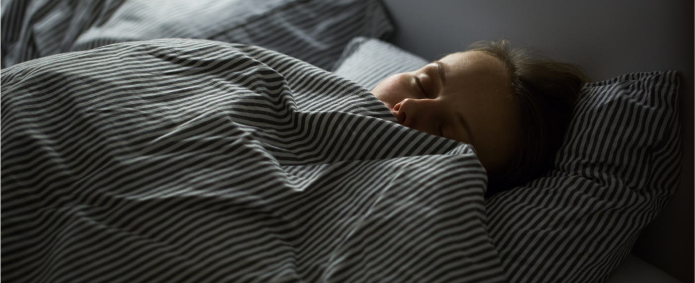 Woman sleeping under striped blankets