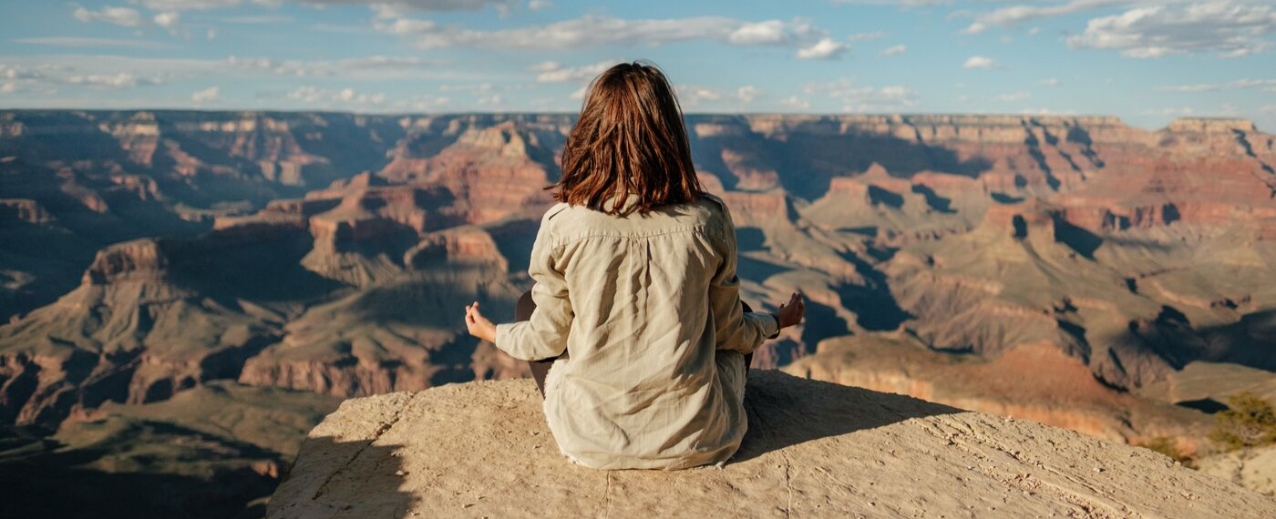 Woman meditating outside overlooking canyons