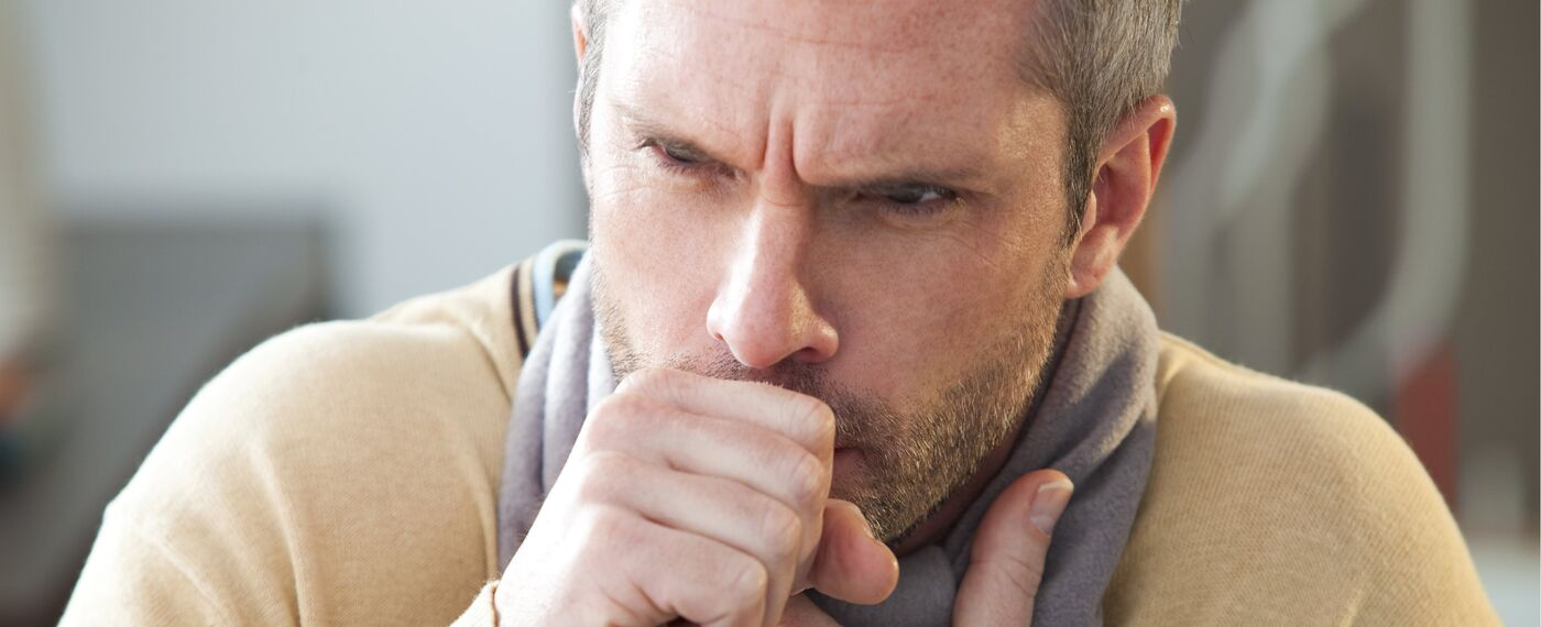 Man coughing while having an asthma attack