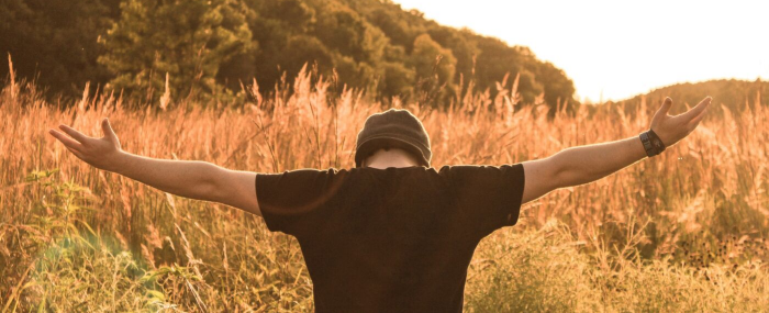 Man standing in a field with outstretched arms