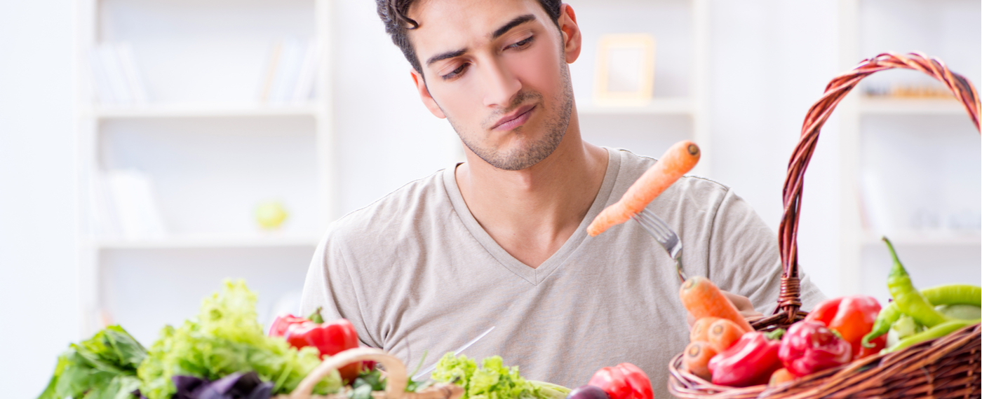 Dark haired man looking at a variety of vegetables