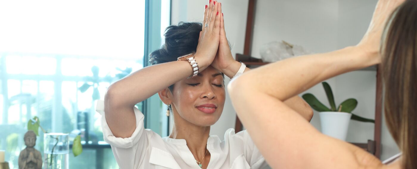 Woman dressed in white meditating with hands at forehead