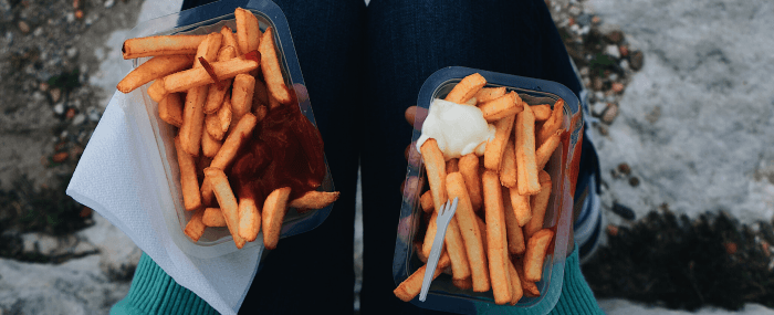two plastic containers of french fries with ketchup