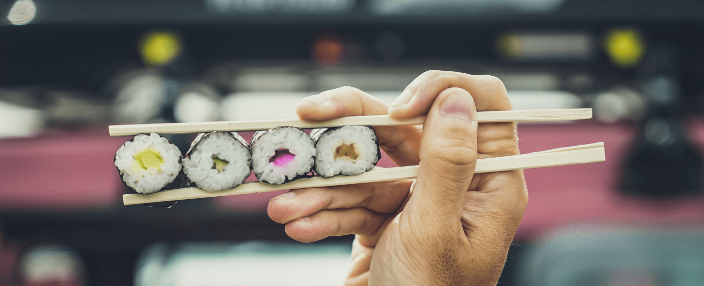 Four sushi rolls in a row being held by one pair of chopsticks