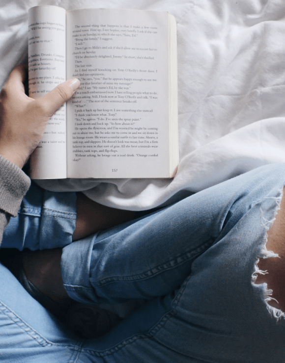 Woman sitting Indian style on bed reading a self-care book