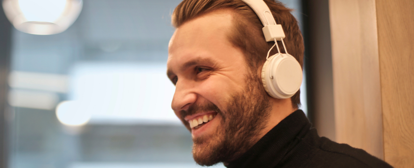 A smiling man with headphones listens to an effective self-care app