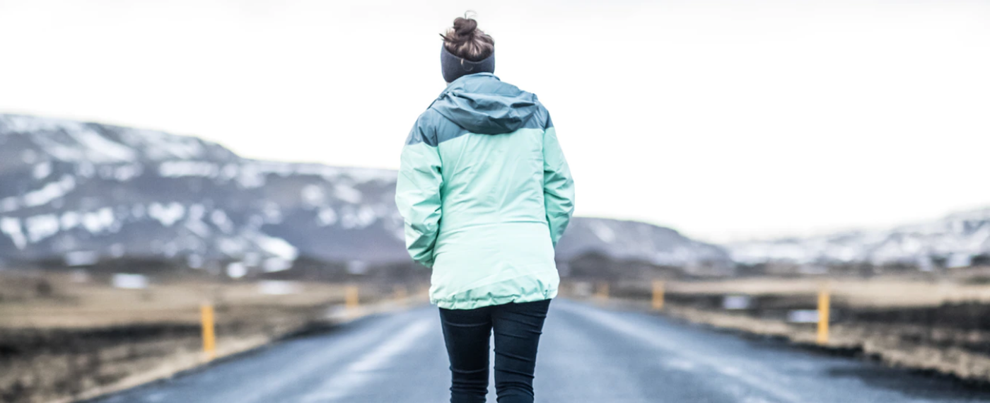 A woman jogs along a snowy road fueled by her winter workout playlist