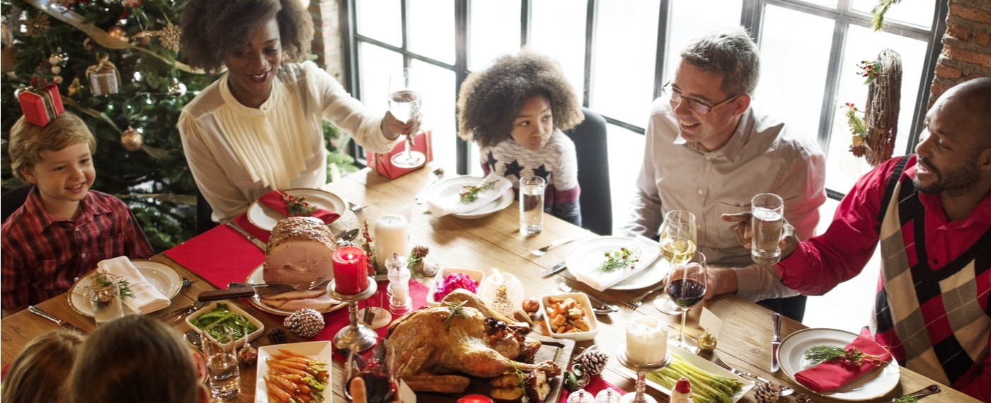 Family sitting a dinner table enjoying a holiday dinner