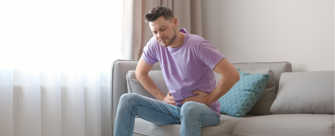 Young man sitting on couch holding his stomach in pain