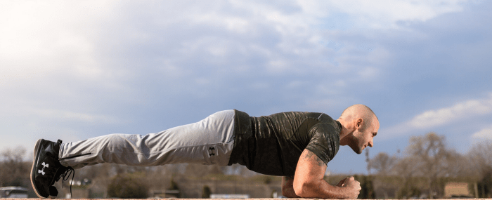 Fit male outdoors holding a plank position
