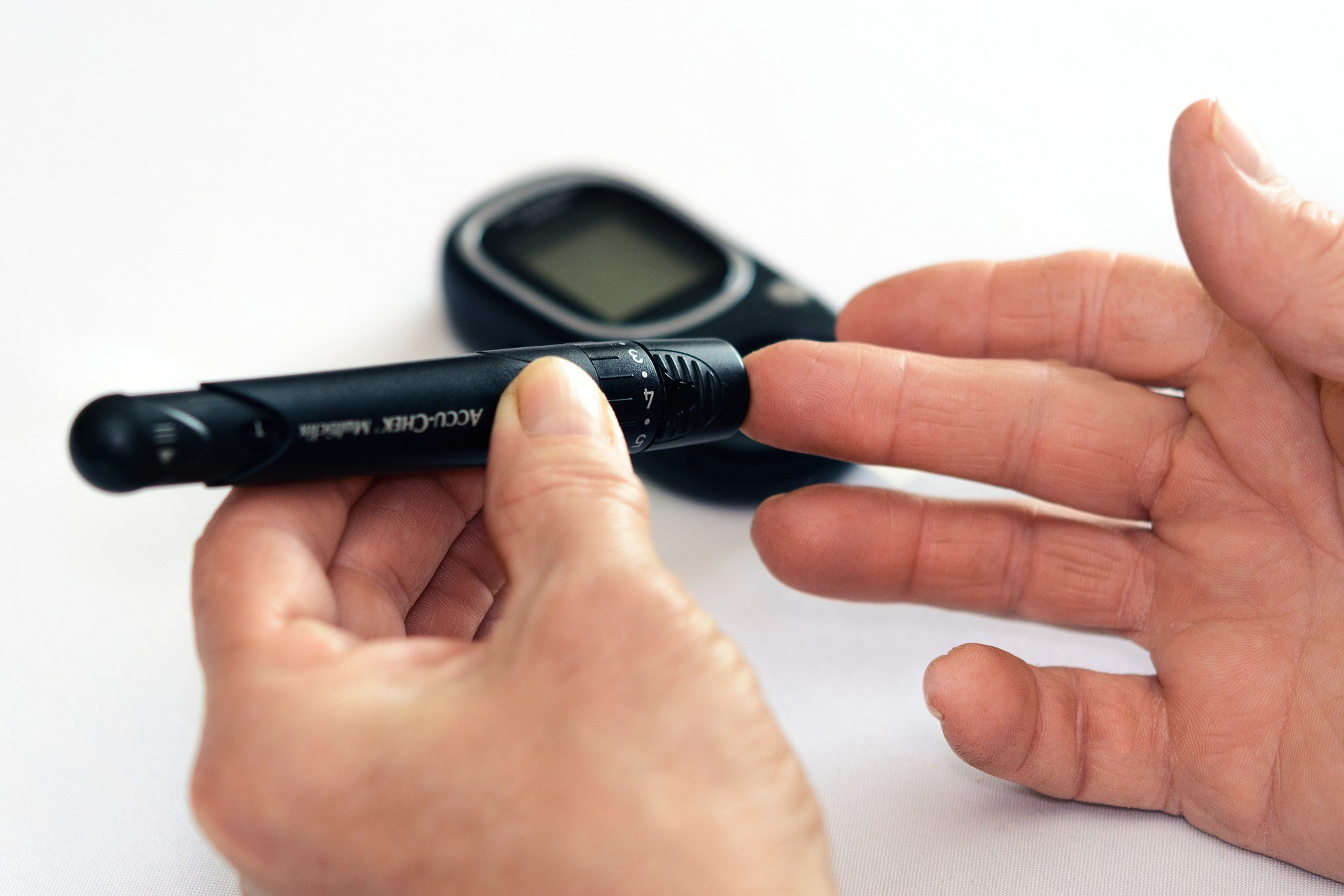 Diabetic male pricking his fingertip with a needle to check blood sugar levels