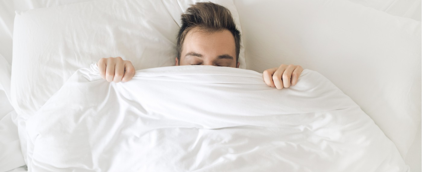 Stress free male sleeping with blanket pulled up over his nose