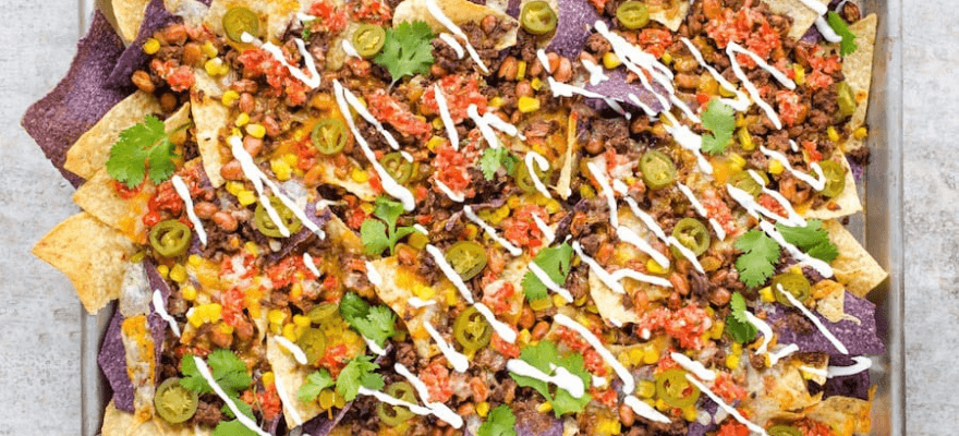 A large tray of loaded healthy nachos with beef and homemade tortilla chips