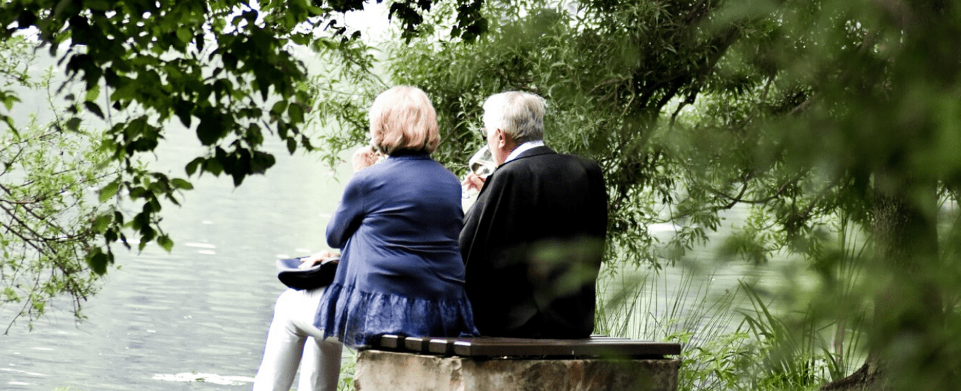 older couple sitting on park bench drinking a glass of wine