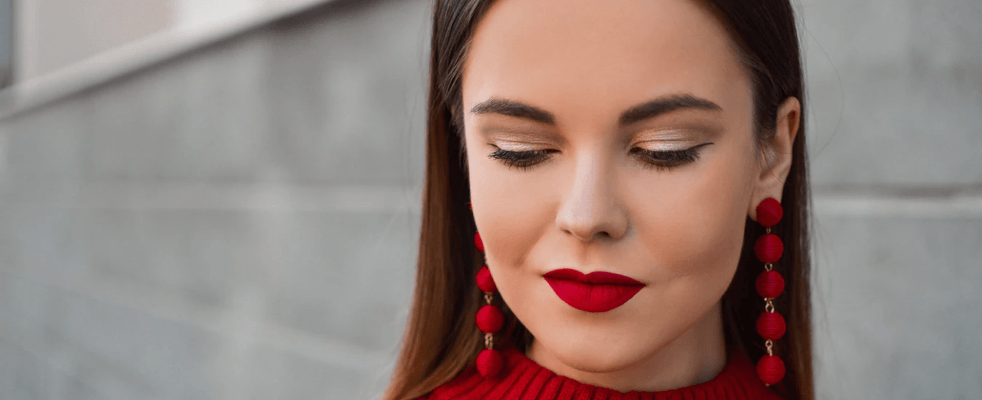 Young woman showing off vibrant red lipstick and dangling earrings