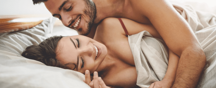 man and woman smiling in bed together