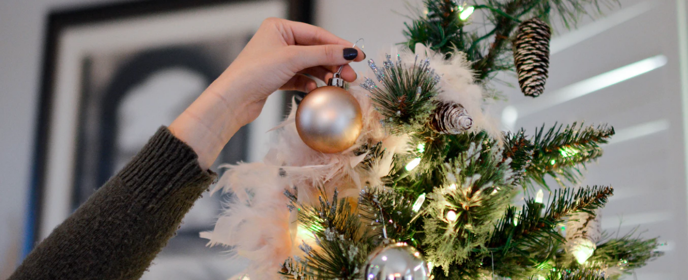 A woman hangs last-minute holiday decor on her Christmas tree