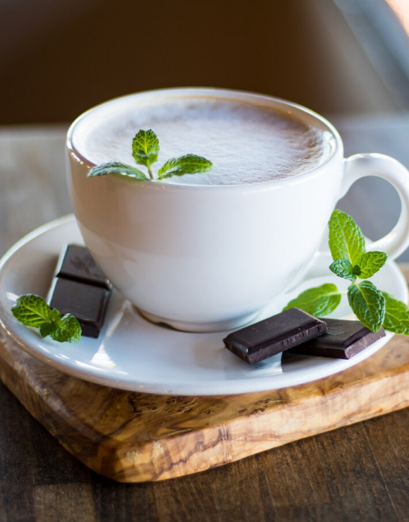 A teacup of peppermint tea with peppermint chocolates on the side
