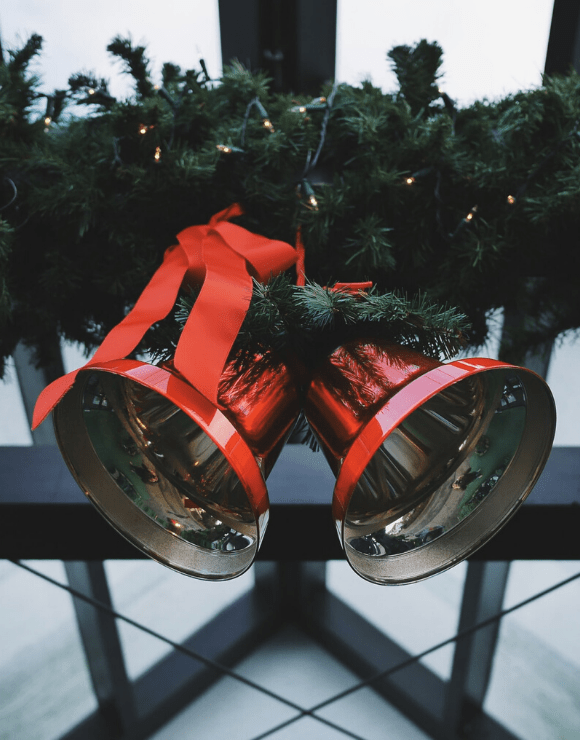 two large holidays bells tied together on a fence by a wreath