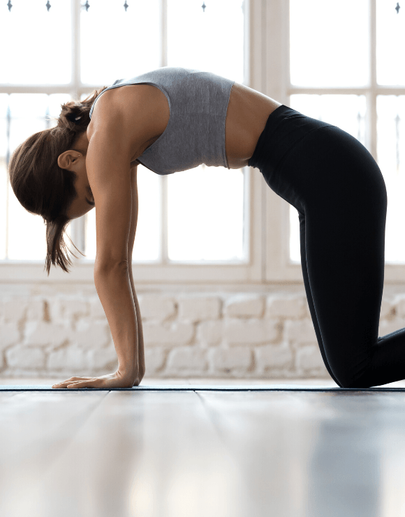 women vacuuming her stomach while practicing yoga