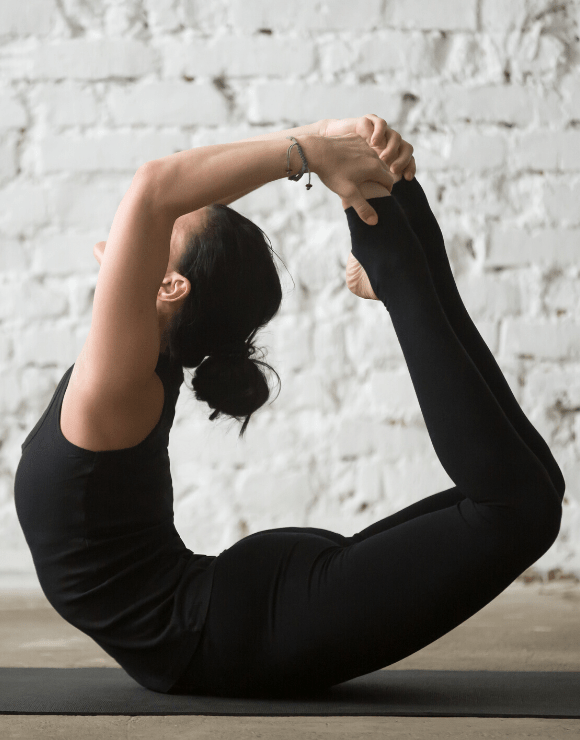 woman doing the Bow Pose Yoga to help stimulate gut health
