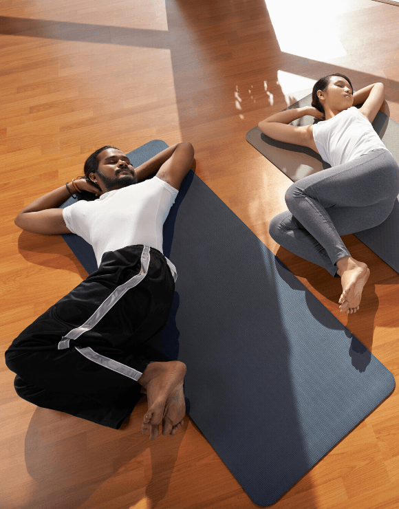 Woman and man lying flat on their backs on a yoga mat stretching their torso to the side