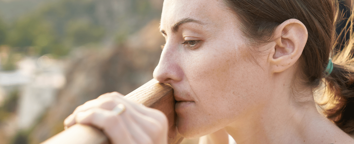 woman leaning against a wooden plank dealing with stress
