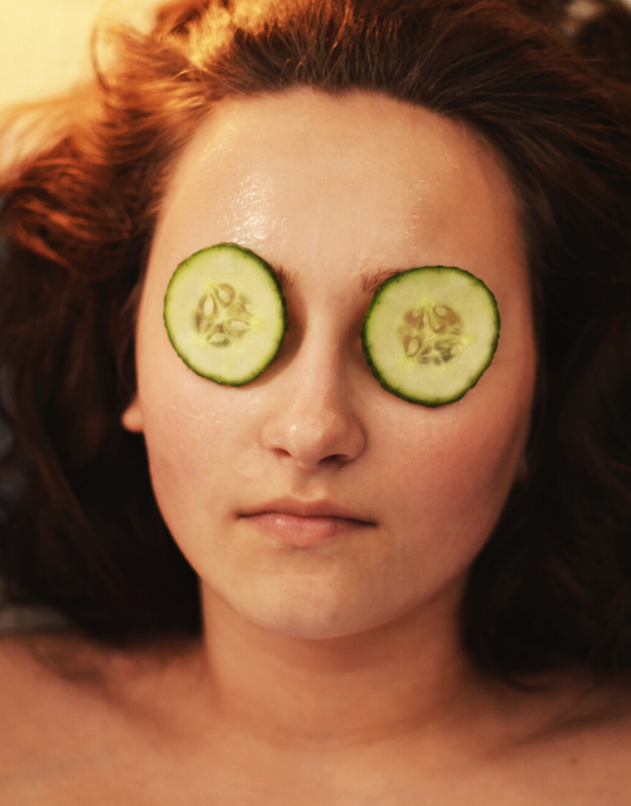 Woman relaxing with cucumber slices resting on her baggy eyes