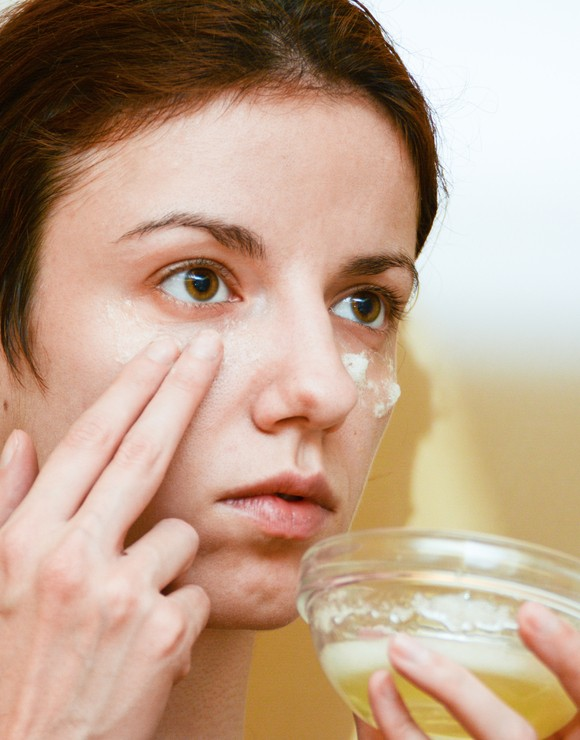 Woman applying raw egg whites to her face to help reduce baggy eyes