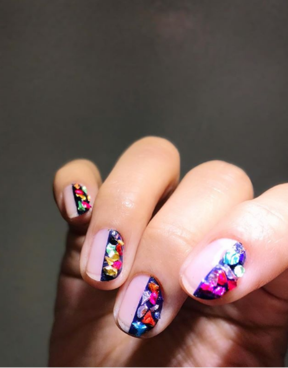 Manicured nails showing nail polish with colorful gems