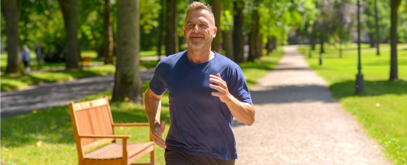 Older male jogging outside on a park path