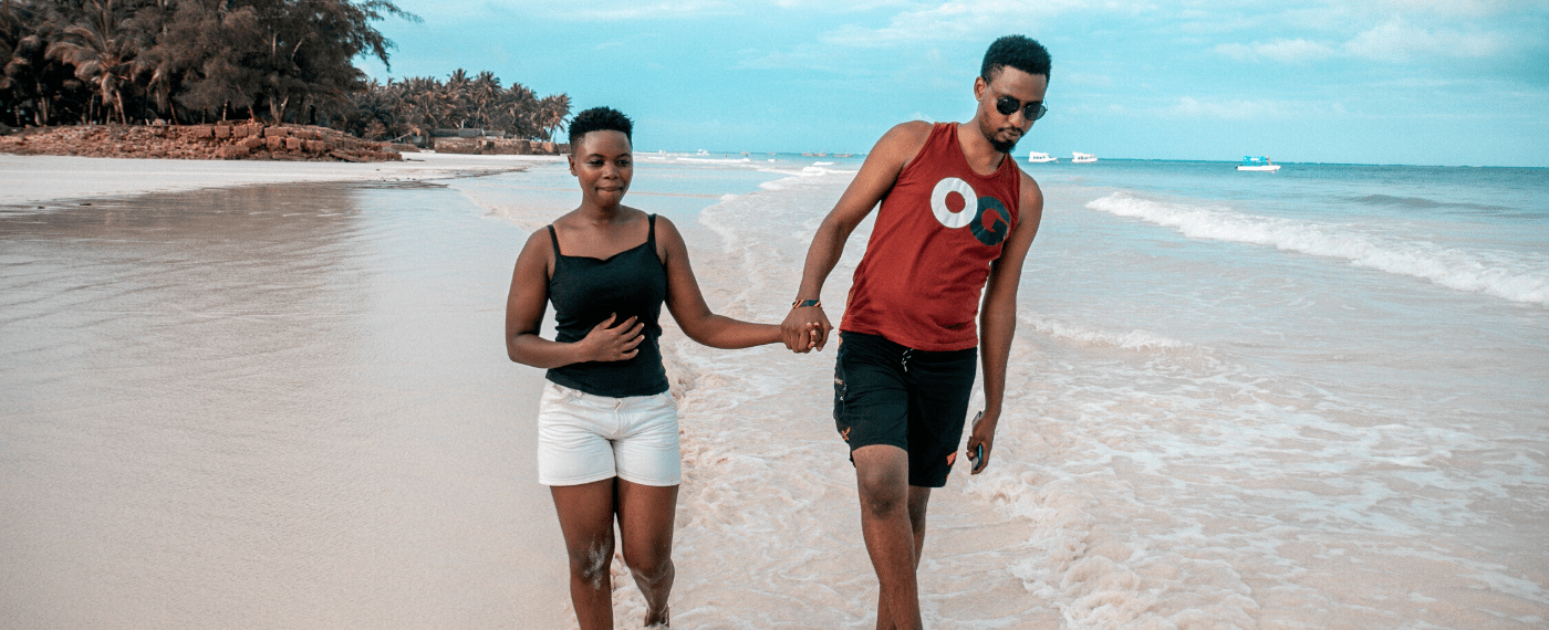man and woman taking a walk on the beach while holding hands