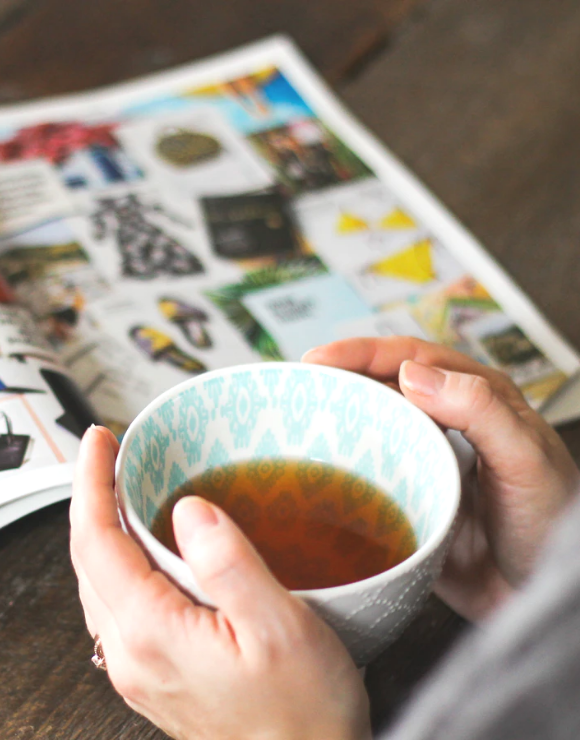 A woman drinks tea while looking at a catalogue