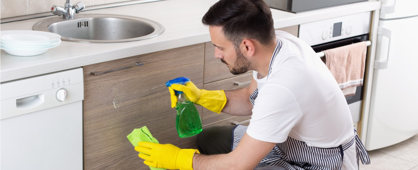 man using natural household cleaner in kitchen