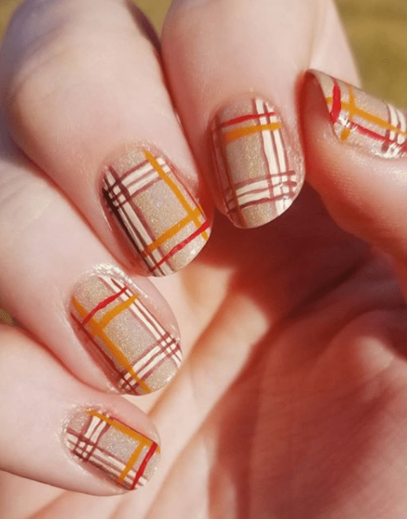 Up close view of a woman's manicure using a plaid nail polish