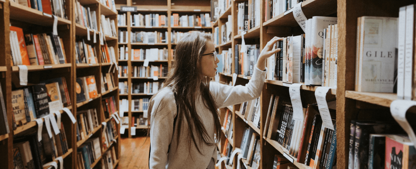 Female student browsing library for self development books